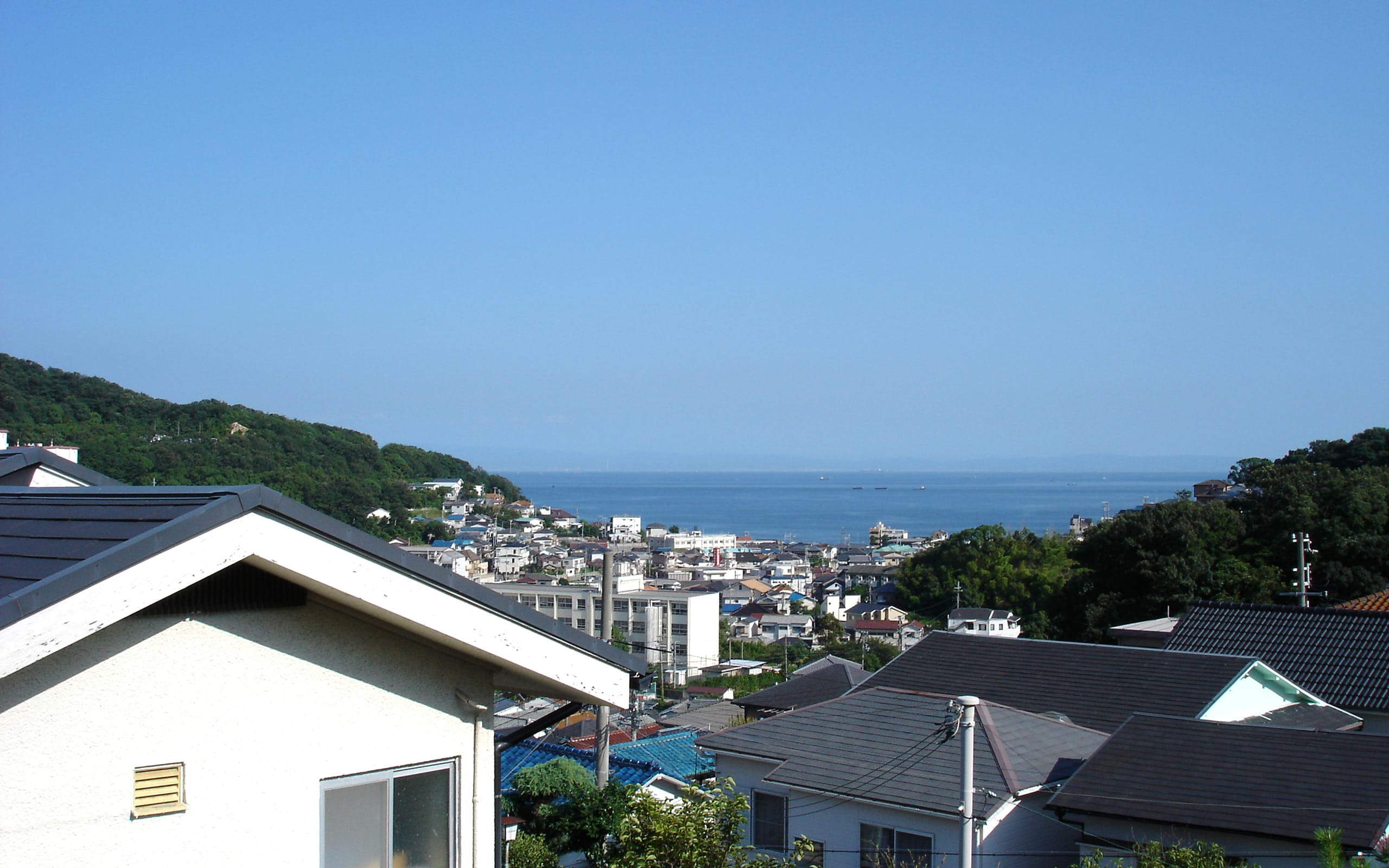 海と山を望む高台にある白い家の眺望1