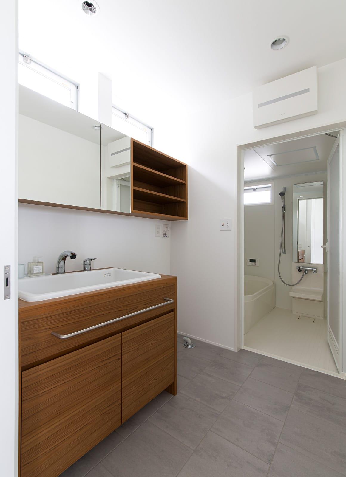傾斜地に建つアウトドアデッキのある家の浴室・洗面室1