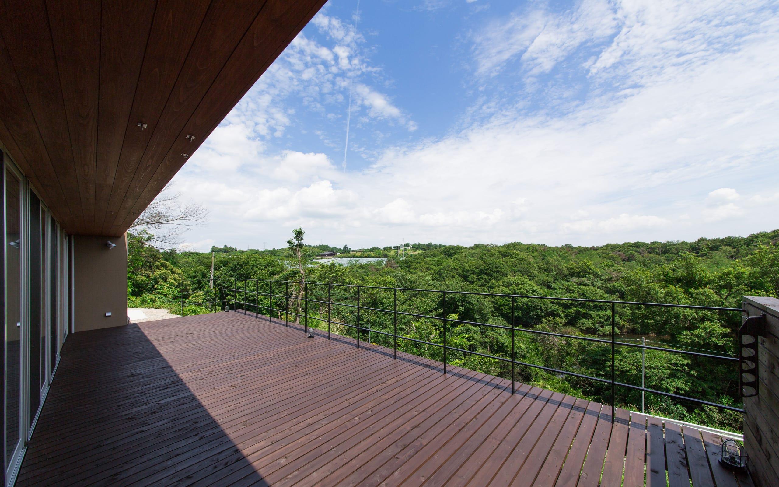 傾斜地に建つアウトドアデッキのある家の外構(デッキテラス)1