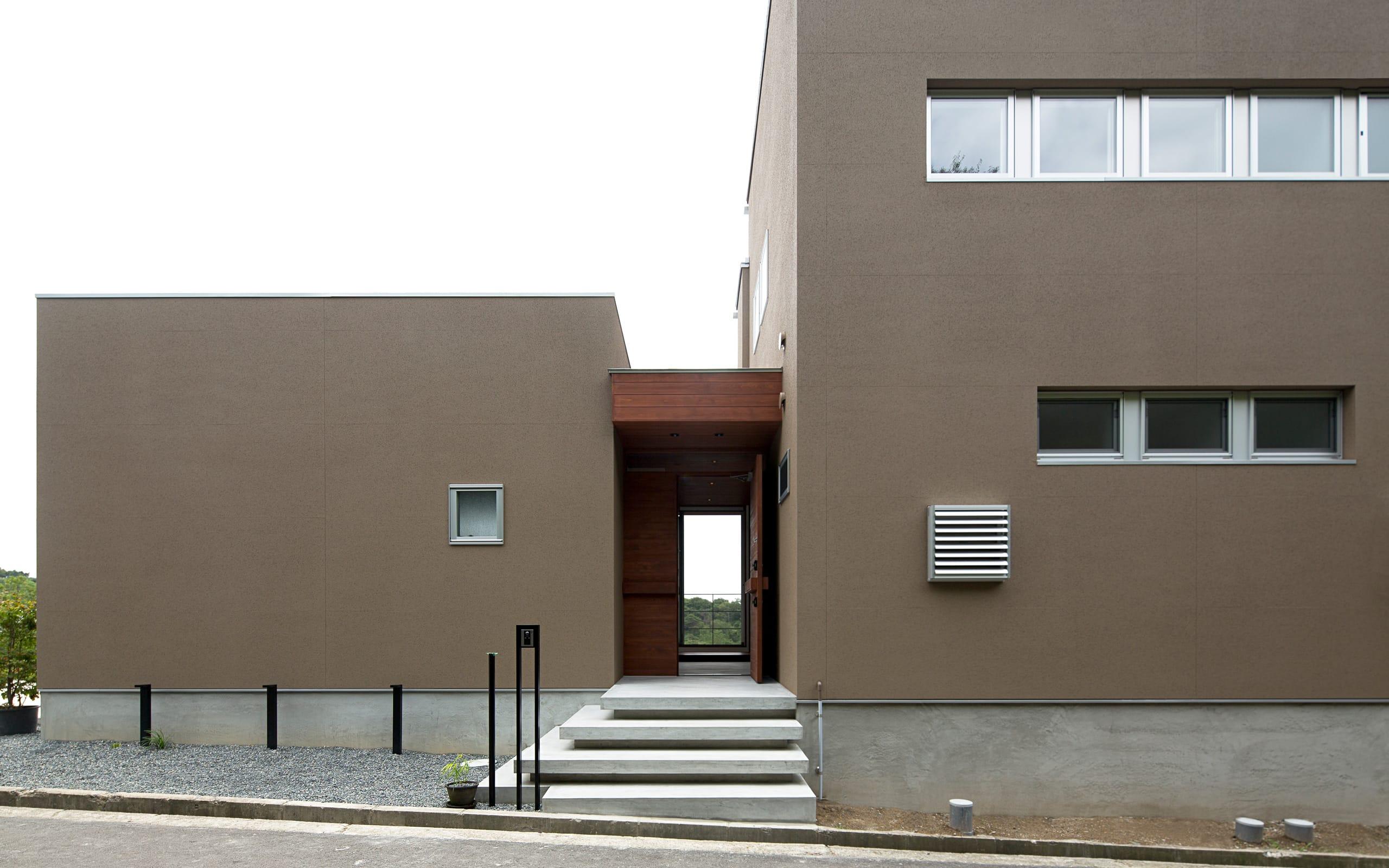 傾斜地に建つアウトドアデッキのある家の外観1