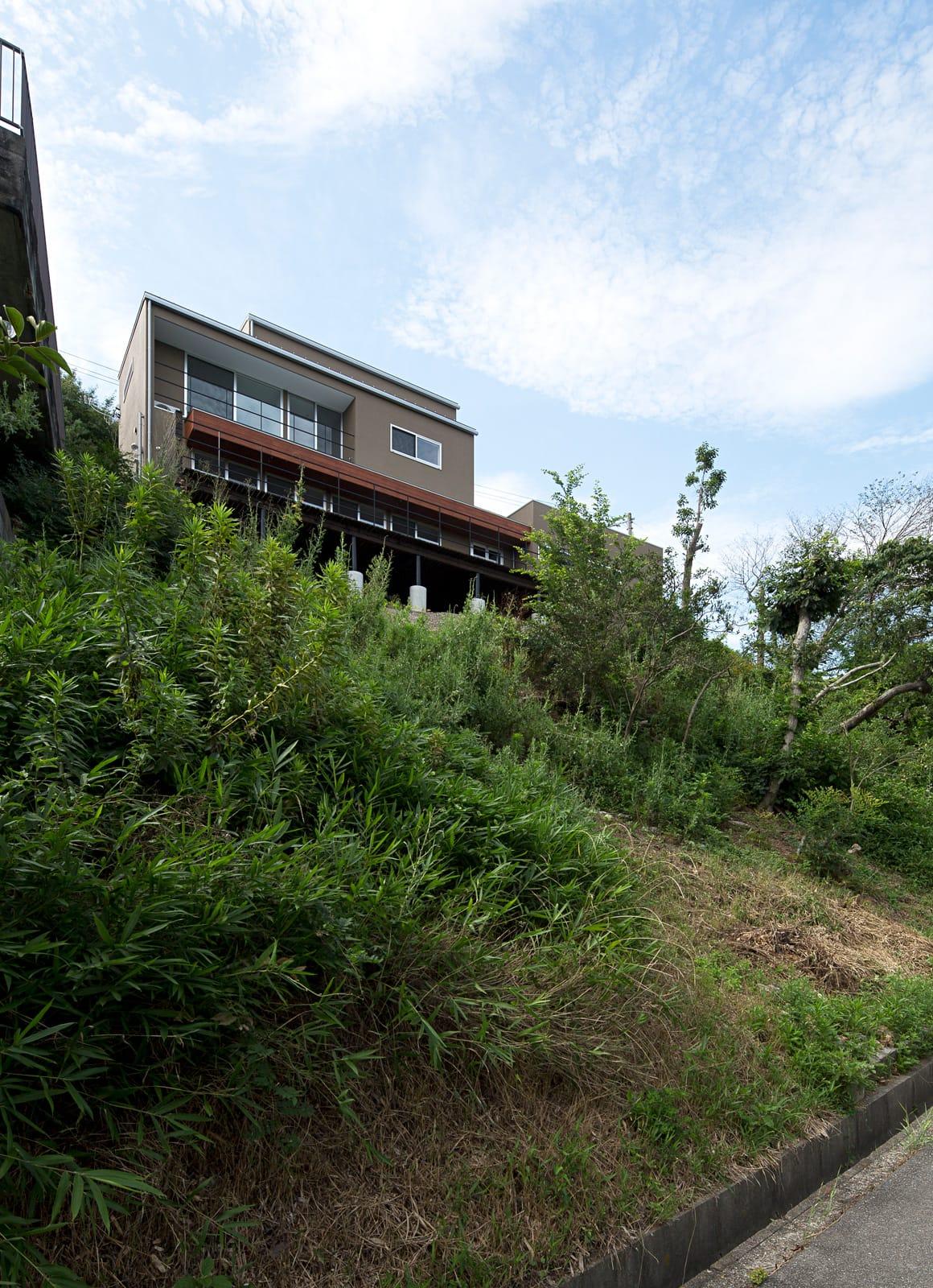傾斜地に建つアウトドアデッキのある家の外観2