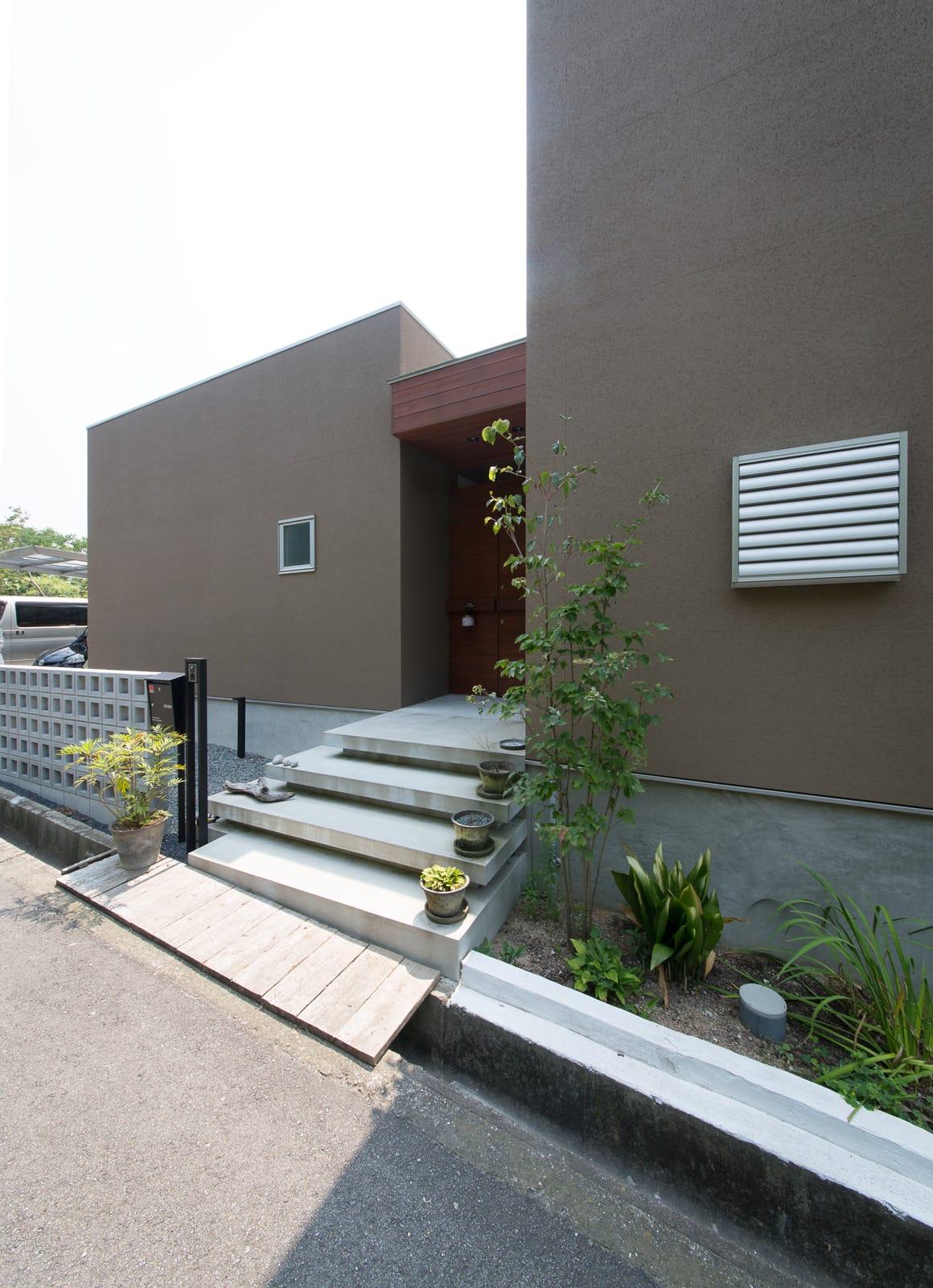 傾斜地に建つアウトドアデッキのある家の外構(ポーチ)1
