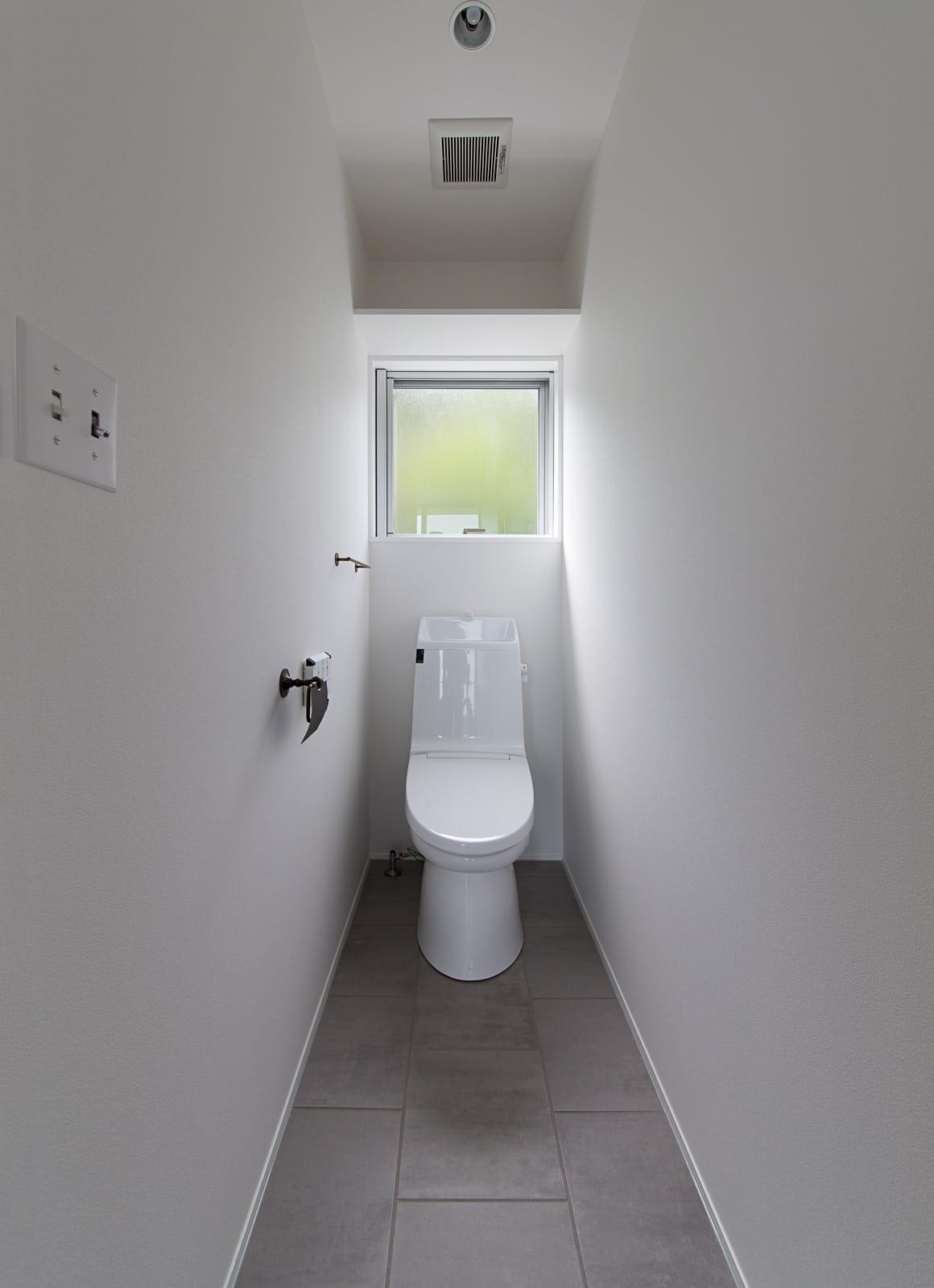 傾斜地に建つアウトドアデッキのある家のトイレ1