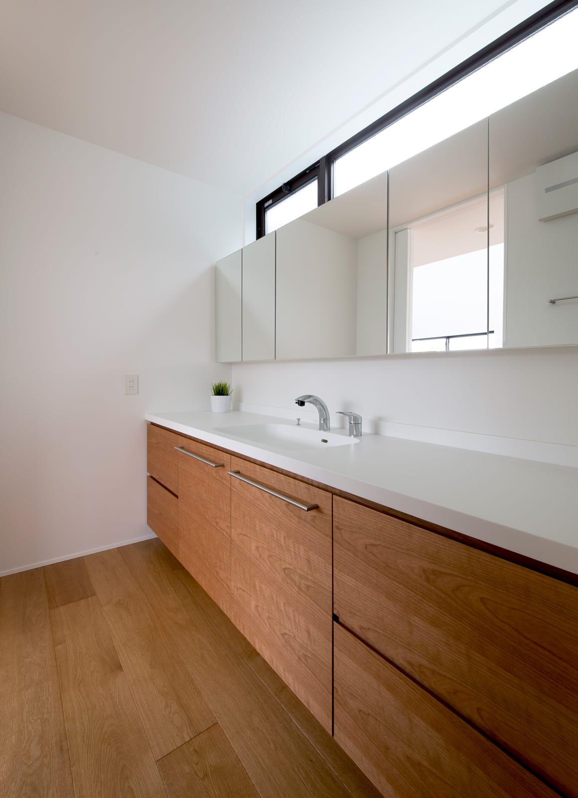 屋上とつながる吹抜リビングの家の浴室・洗面室1