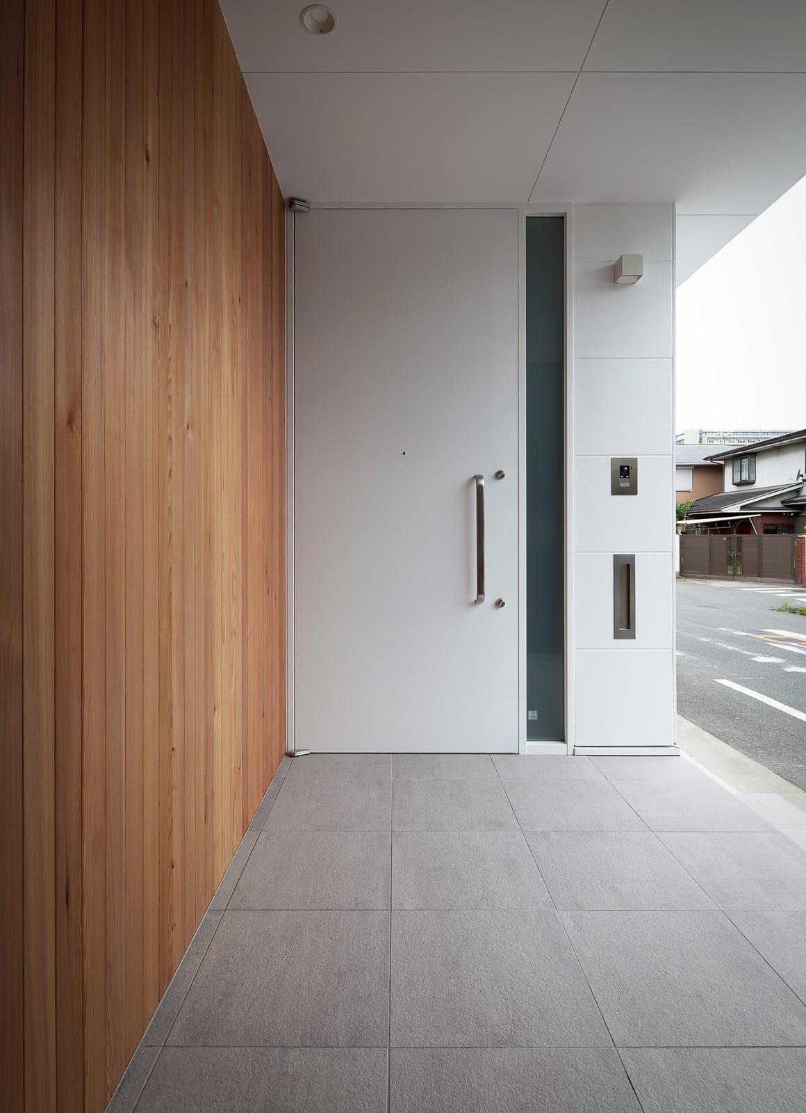屋上とつながる吹抜リビングの家のポーチ・玄関扉1